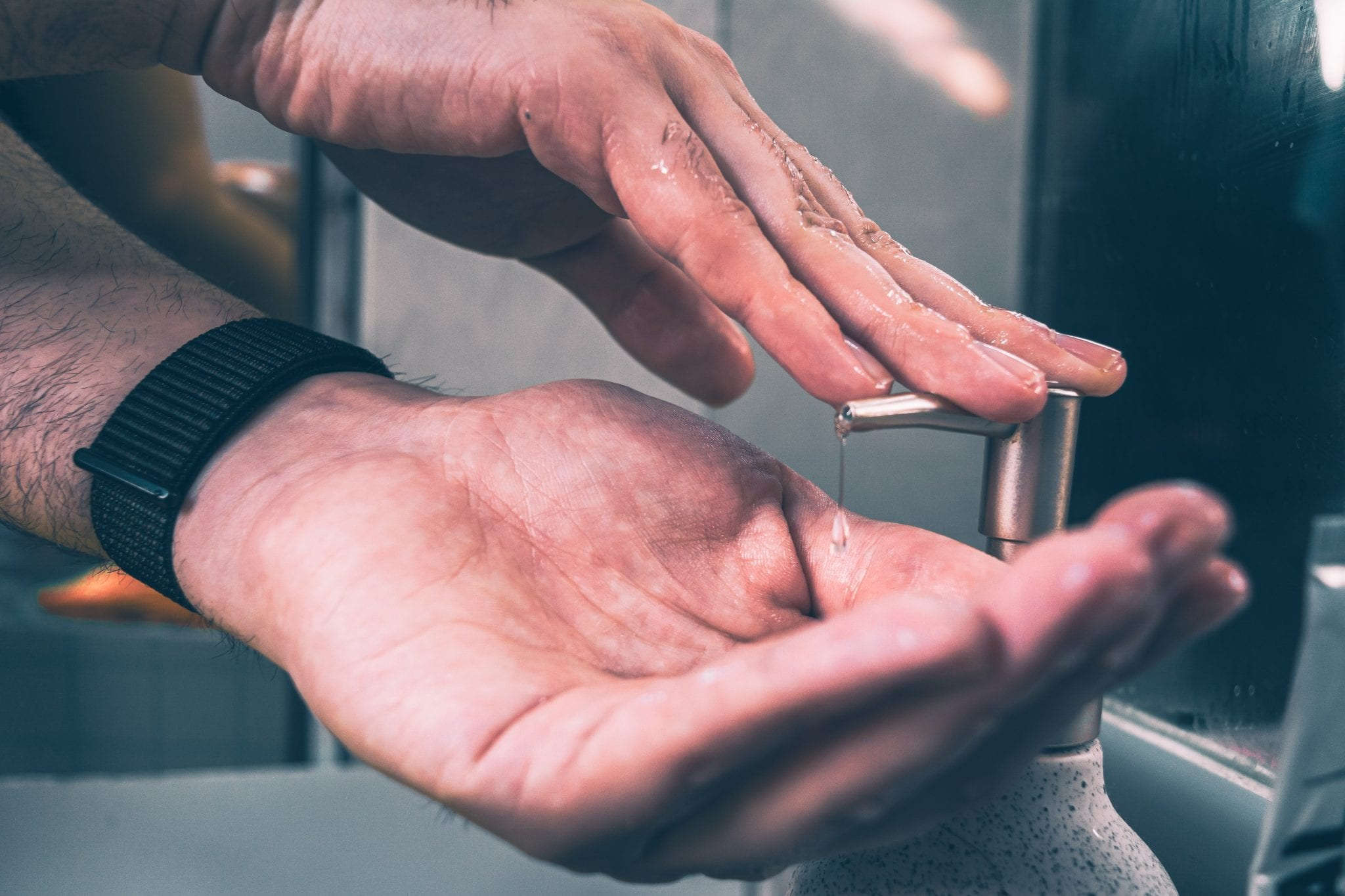 Masculine hands applying soap, photo by Christine Sandu via Unsplash